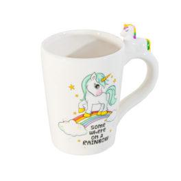 Taza blanca con un dibujo de un Unicornio encima de un arcoiris y un unicornio en relieve en la asa.